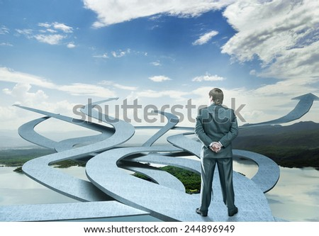 Businessman stands choosing his way - stock photo