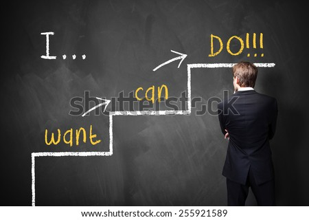businessman stands in front of a blackboard with a motivational message - stock photo