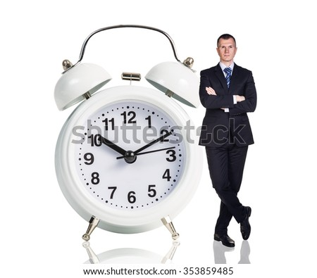 Businessman stands near big white alarm clock isolated on the white