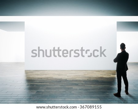 Businessman stands opposite big white wall in museum interior with wooden floor. Horizontal - stock photo
