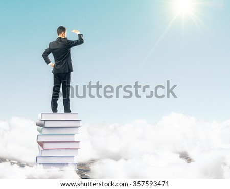 Businessman staying on the pile of books on the top among clouds and looking into the distance - stock photo