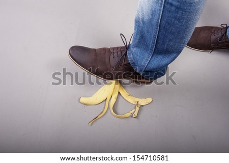 Businessman step into banana peel - stock photo
