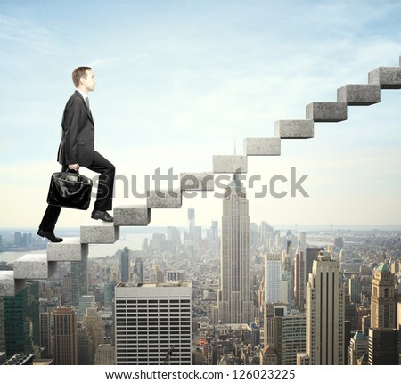 Businessman stepping up a staircase and city