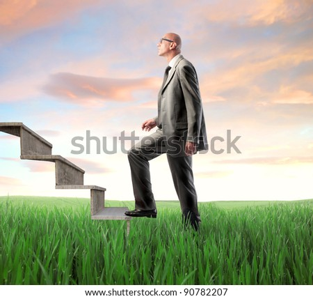 Businessman stepping up a stairway from a green meadow - stock photo