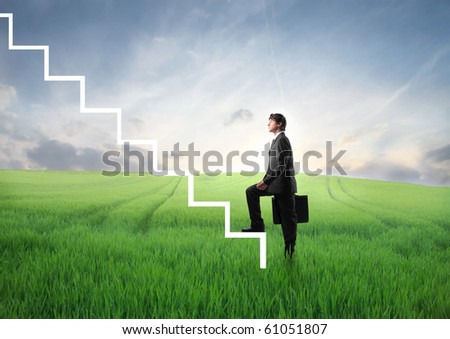 Businessman stepping up the stairs from a green meadow - stock photo