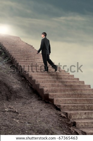 Businessman stepping up to a stairway - stock photo