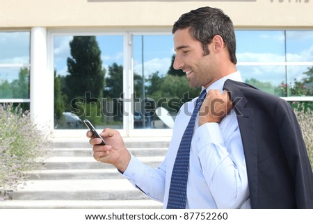 Businessman stood outdoors sending text message from telephone - stock photo