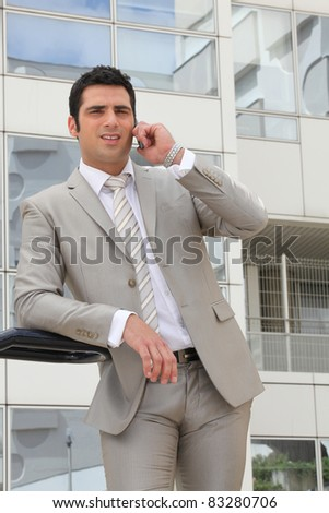 Businessman stood outside office with mobile telephone - stock photo