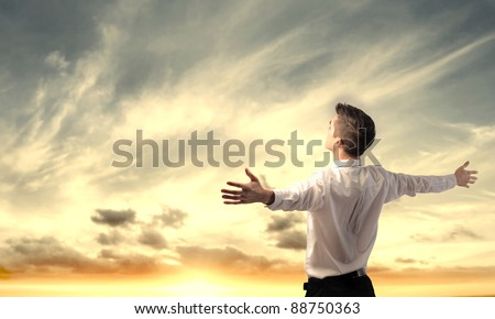 Businessman stretching out his arms in front of a sunrise - stock photo