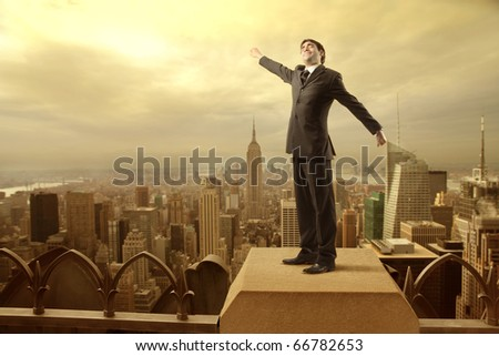 Businessman stretching out on the rooftop of a skyscraper over a city - stock photo