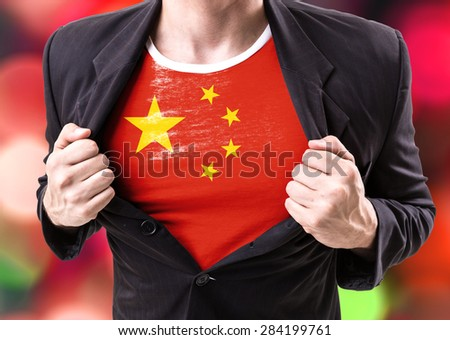 Businessman stretching suit with Chinese Flag on bokeh background - stock photo