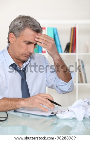 Businessman struggling at his desk - stock photo