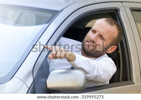 Businessman stuck in the traffic gesturing angry