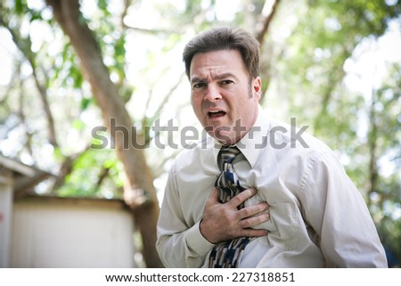 Businessman suffering chest or stomach pain related to heart attack, angina, or other illenss like flu or ebola.   - stock photo