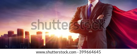 Businessman Superhero With Red Cape Dominates The City  - stock photo