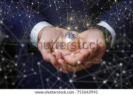 Businessman Supports Bitcoins In Hands On Dark Background