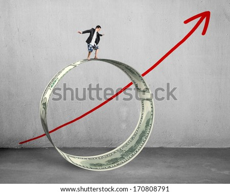 Businessman surfing on money circle with growing red arrow concrete background - stock photo