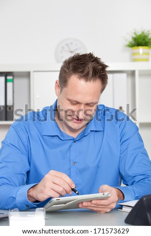 Businessman surfing the internet on a tablet-pc using a stylus on the touchscreen as he sits working at his desk in the office