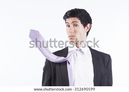 Businessman surprised with his flying necktie (isolated on gray) - stock photo