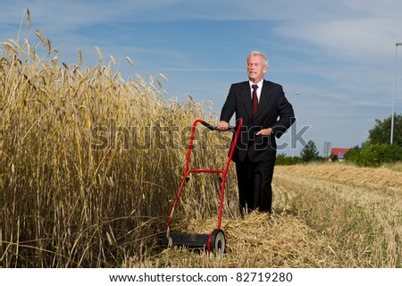 Businessman surveying a challenge with courage and determination as he assesses a large field of ripe golden wheat ready for harvesting with just a hand mower at his disposal - stock photo