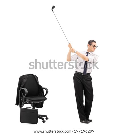 Businessman swinging a golf bat with an office chair beside him isolated on white background shot with tilt and shift lens