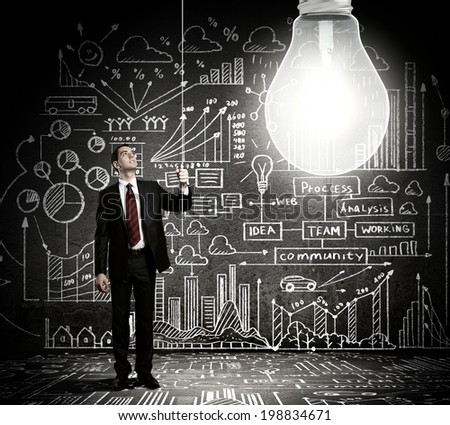 Businessman switching on light bulb with business sketches at background - stock photo