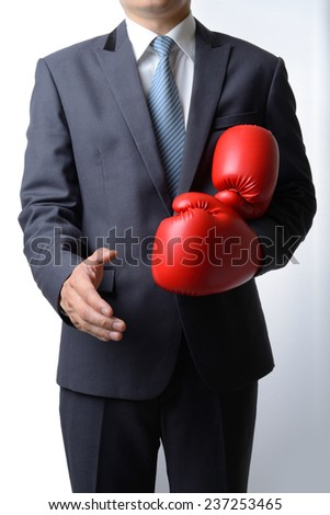 Businessman take off red boxing gloves to offer a handshake on white background,compromise concept - stock photo