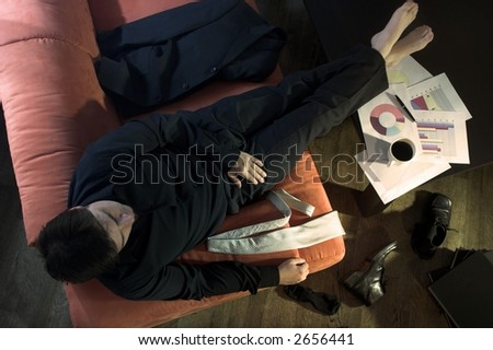 Businessman takes a break on the couch. - stock photo