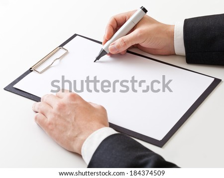 Businessman takes notes on clipboard with copyspace - stock photo