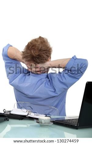 Businessman taking a break at his desk - stock photo