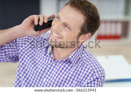 Businessman taking a call in the office on a telephone smiling broadly with pleasure as he listens to the conversation, close up head and shoulders - stock photo