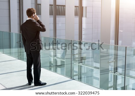 Businessman taking a call on smartphone in office building - stock photo