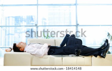 Businessman taking break at office, lying on back and thinking while resting on sofa and holding laptop computer.