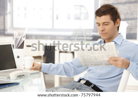 Businessman taking break in office, reading newspaper, having coffee, putting phone aside.? - stock photo