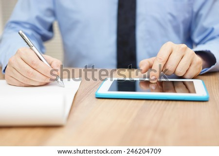 Businessman taking business notes and working on tablet computer - stock photo