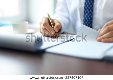 Businessman taking business notes at office  - stock photo