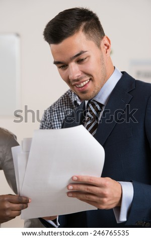 Businessman taking contract documents from his colleague at office . Business team working - stock photo
