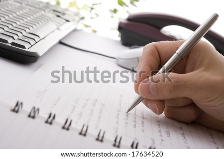 Businessman taking notes and planning in a meeting - stock photo