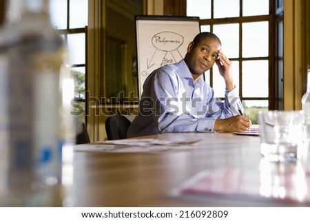 Businessman taking notes at table by whiteboard, head in hand, low angle view - stock photo