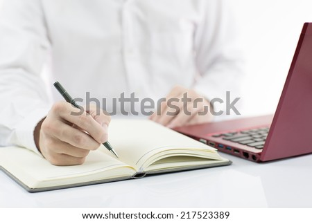 Businessman taking notes with laptop background - stock photo