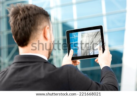 Businessman taking photo of contemporary building with digital tablet - stock photo