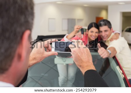 Businessman taking picture of the couple in their new car at new car showroom - stock photo