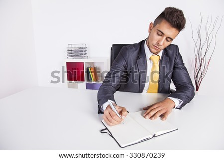 Businessman taking some notes on his notepad at his office - stock photo