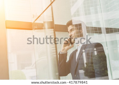 Businessman talk to cellphone and look out of window - stock photo