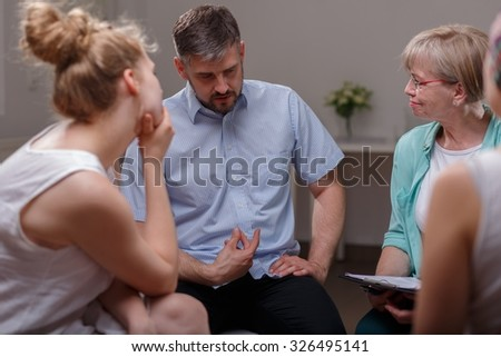 Businessman talking about his problems during group therapy session - stock photo