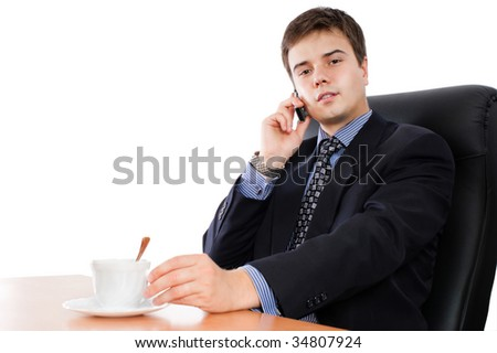 Businessman talking by cellphone with cup of coffee in an office environment - stock photo