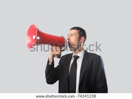 Businessman talking in a megaphone - stock photo