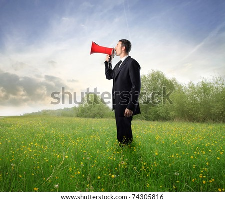 Businessman talking in a megaphone on a green meadow - stock photo