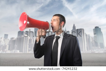 Businessman talking in a megaphone with cityscape on the background - stock photo