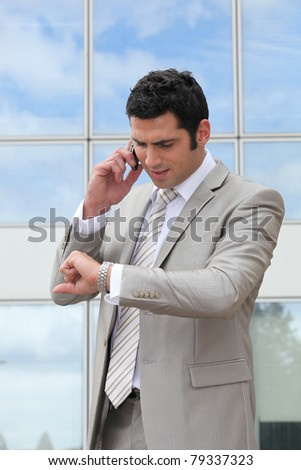 Businessman talking on a cell and checking his watch - stock photo